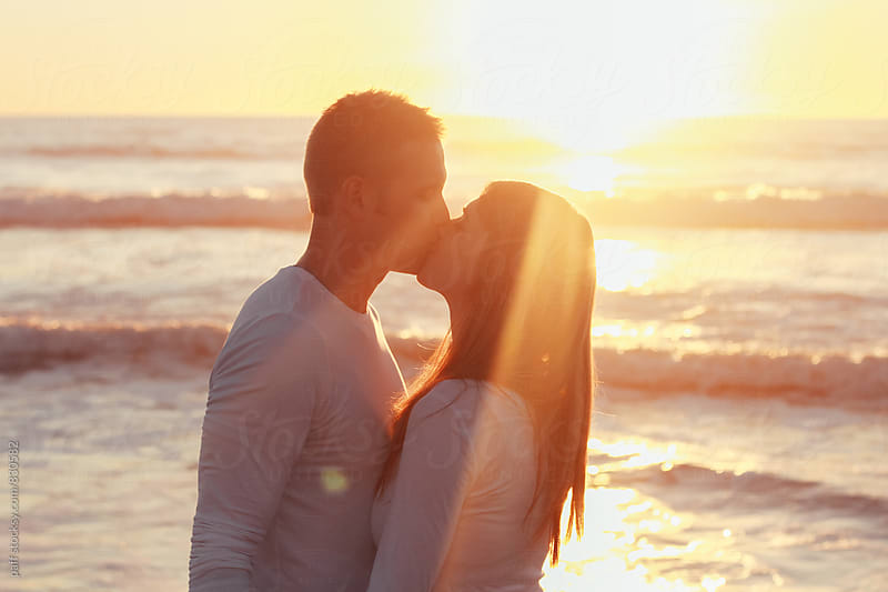 Young couple kissing on the beach at sunset by paff for Stocksy United