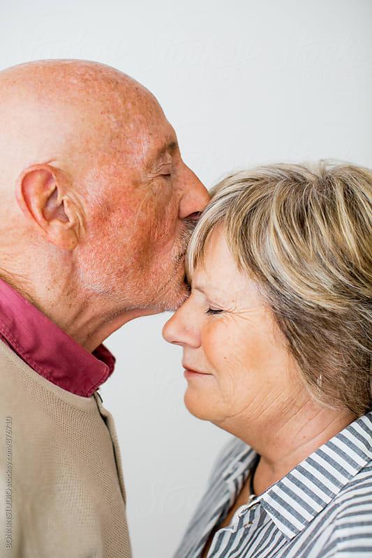 Elderly couple kissing on white. by BONNINSTUDIO for Stocksy United
