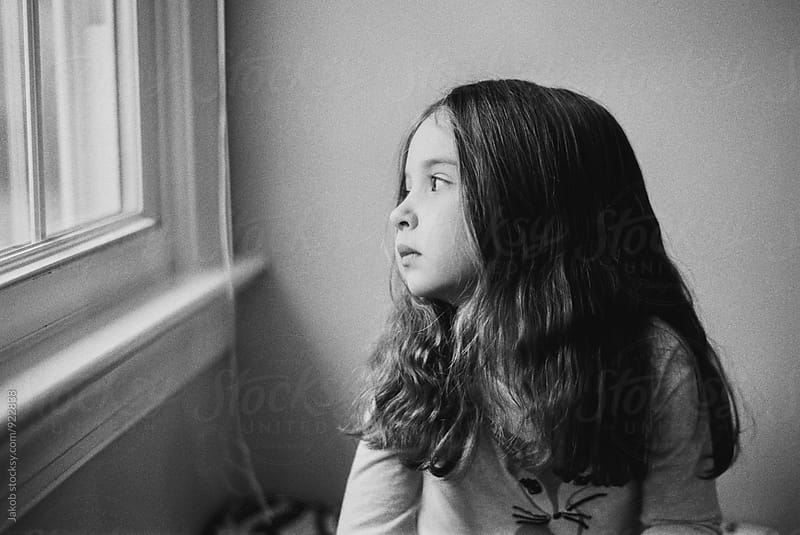 Cute young girl looking bored while peeking out a window by Jakob for Stocksy United