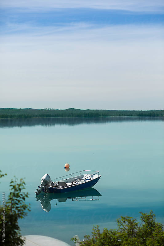 Boat with an Outboard Engine Floating on a Turquoise Lake by Willie Dalton for Stocksy United
