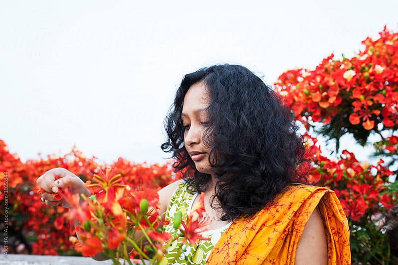 Young woman plucking flower by PARTHA PAL for Stocksy United