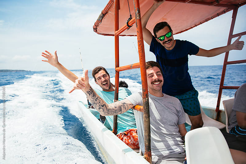 Three young hipster men having fun during a boat trip in the sea on a sunny day by Alejandro Moreno de Carlos for Stocksy United