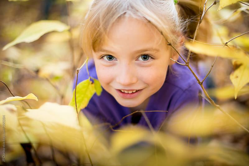 Little Girl Hiding In Yellow Fall Leaves In Autumn by JP Danko for Stocksy United