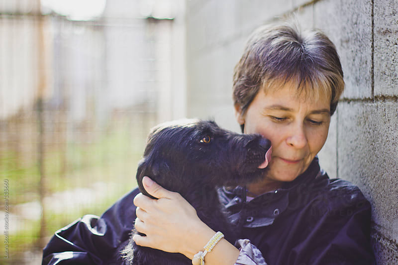 Little crossbreed dog kisses a woman on her cheek by Laura Stolfi for Stocksy United