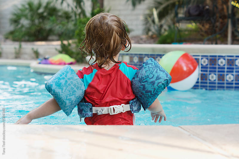 little boy wearing floating vest plays in pool by Tana Teel for Stocksy United