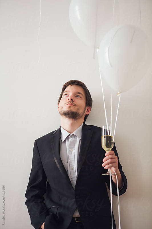 Man With Champagne and Balloons by Lumina for Stocksy United