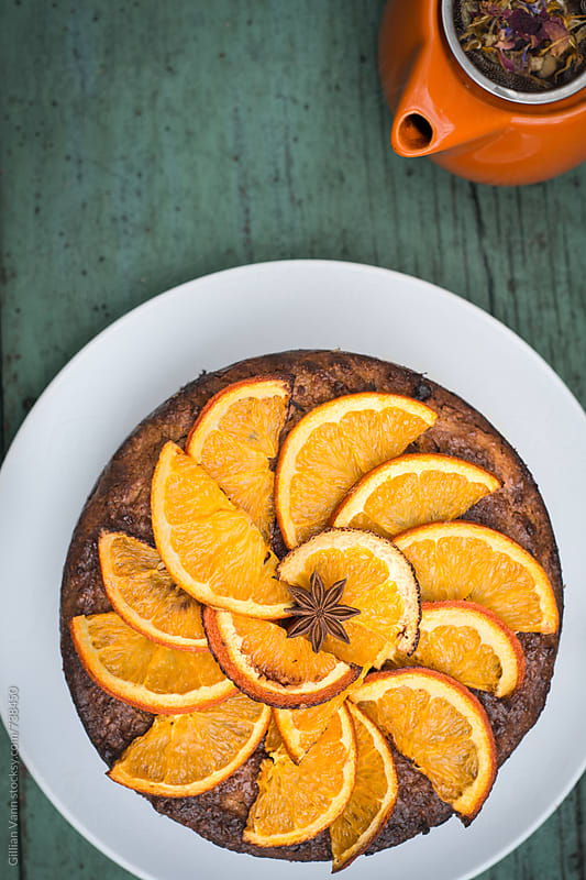 orange and almond cake, with orange tea pot by Gillian Vann for Stocksy United
