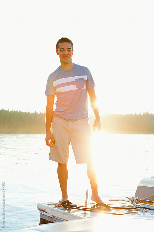 Man standing on a dock at sunset by Linzy Slusher for Stocksy United
