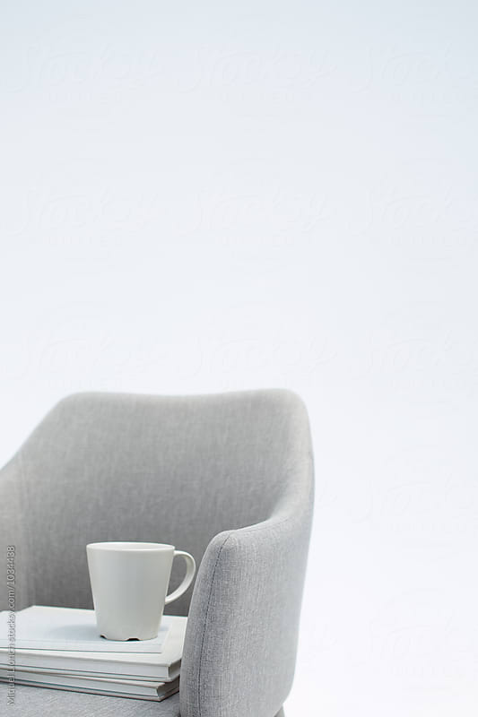 Grey seat with books and a mug with white background by Miquel Llonch for Stocksy United