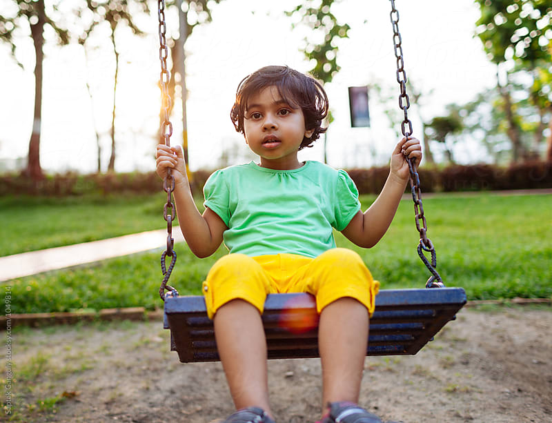 Child in contemplative mood in a swing at a park by Saptak Ganguly for Stocksy United