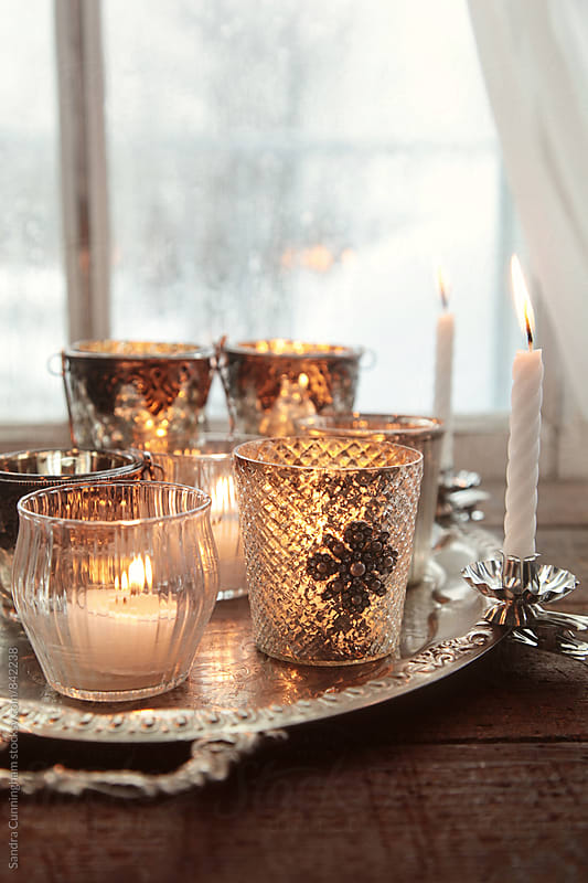 Closeup of candles in front of window by Sandra Cunningham for Stocksy United