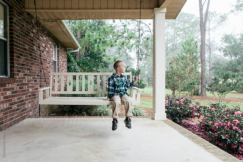 Boy on Porch Swing by Stephen Morris for Stocksy United