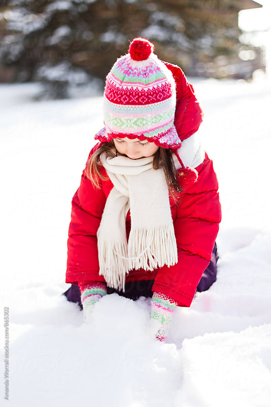 Young girl wearing colorful snow gear scoops up snow in her mittens by Amanda Worrall for Stocksy United