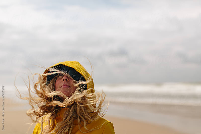 Blond woman daydreaming on a windy beach with her hair  by Denni Van Huis for Stocksy United