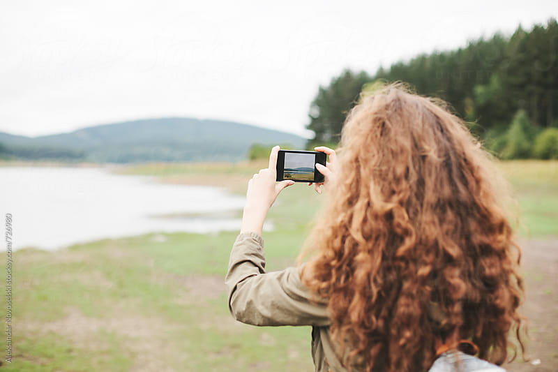Young woman taking pictures with her smartphone in nature by Aleksandar Novoselski for Stocksy United