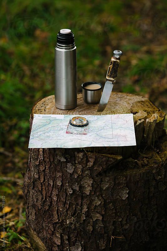 Map and a compass with coffee and a knife. by Darren Muir for Stocksy United