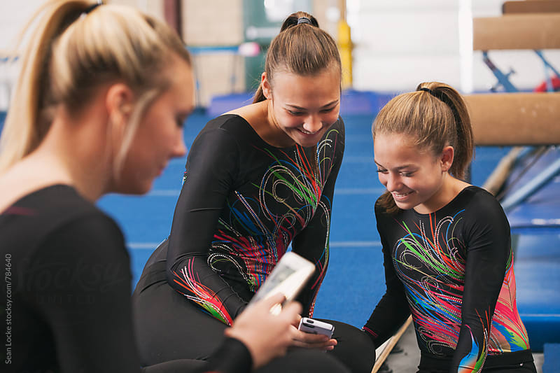 Gymnastics: Friends Take A Break To Look At Text Message by Sean Locke for Stocksy United
