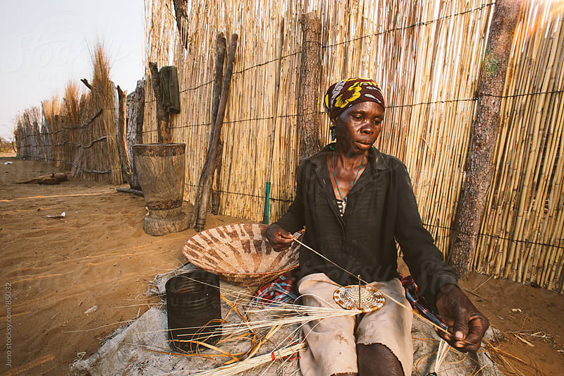 African Hambukushu woman weaving reed baskets by Micky Wiswedel for Stocksy United