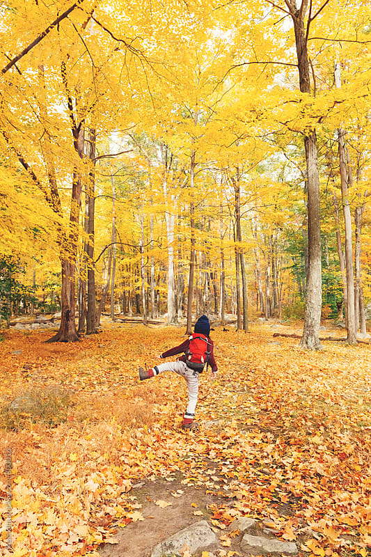 Young boy doing jig in autumn forest by Kelli Seeger Kim for Stocksy United