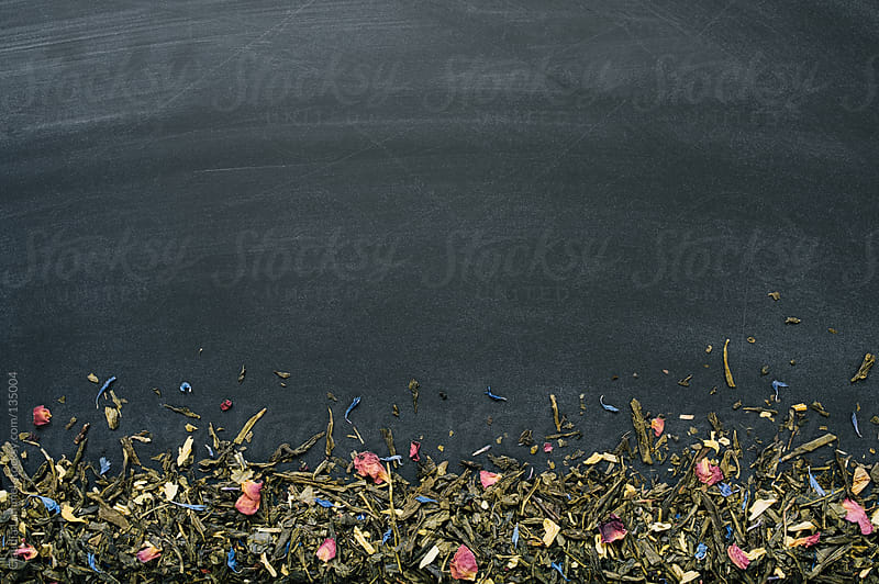 Loose Green Tea Flower Petals on Chalkboard Background  by Claudia Lommel for Stocksy United