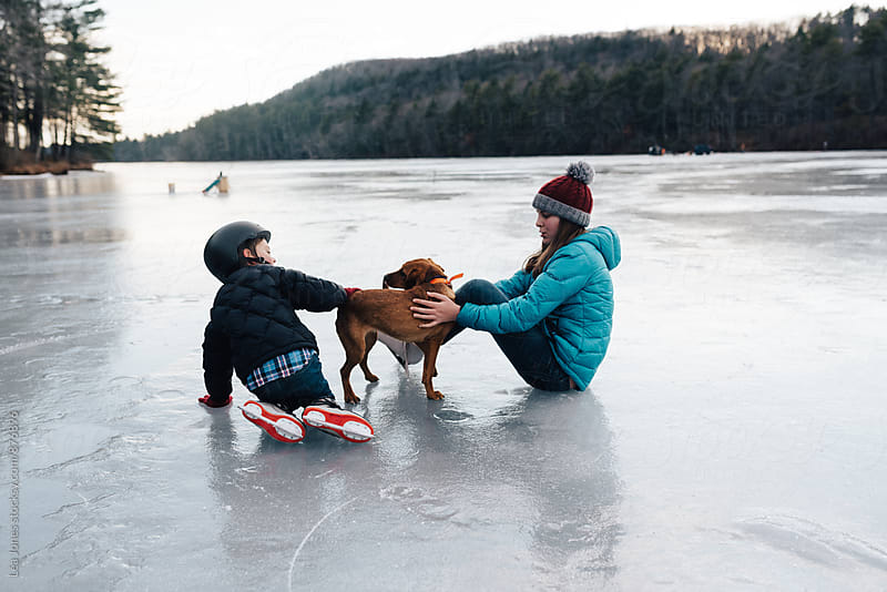 kids playing with  a puppy on frozen lake by Léa Jones for Stocksy United