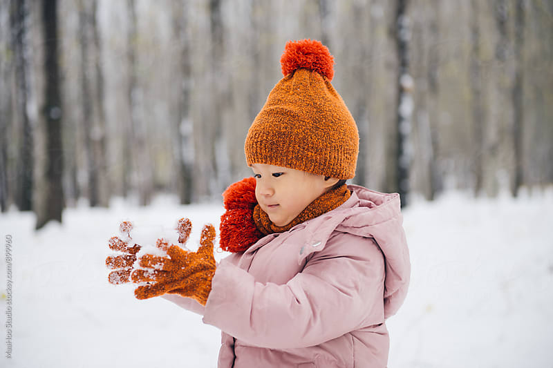 Toddle girl playing in a forest full of snow by MaaHoo Studio for Stocksy United