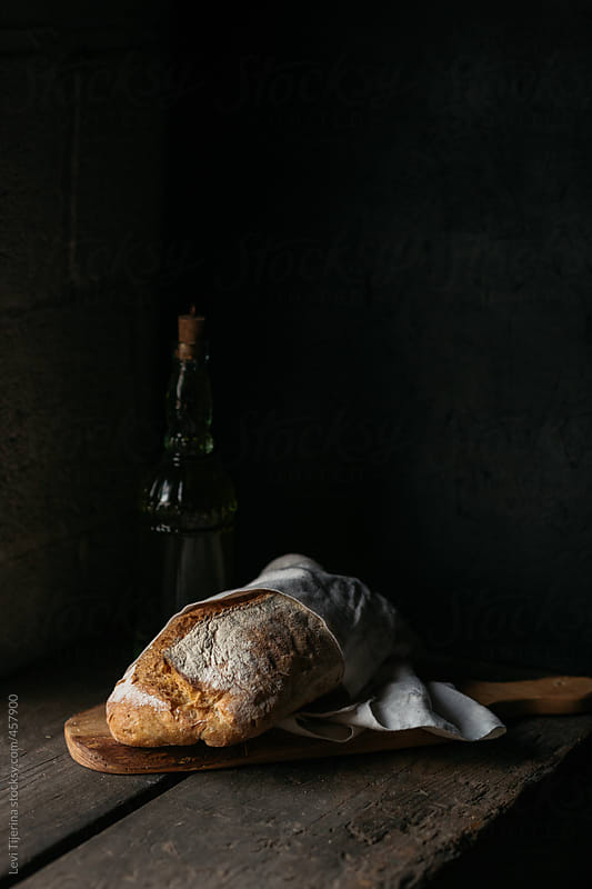 artisanal loaf of fresh bread in dark moody kitchen by Levi Tijerina for Stocksy United