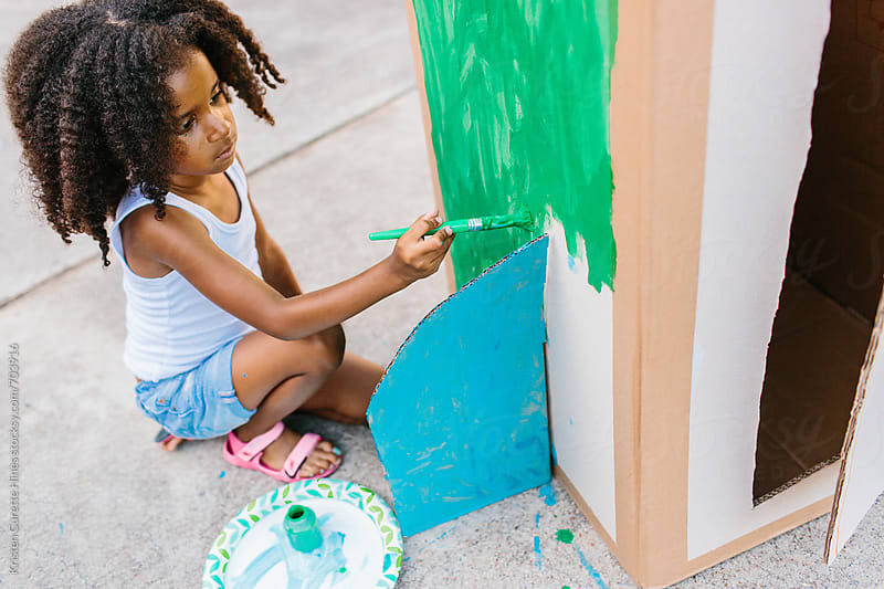 A small child outdoors painting her cardboard box spaceship green by Kristen Curette Hines for Stocksy United