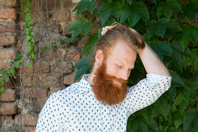 Smiling redhead man against the wall by Alberto Bogo for Stocksy United