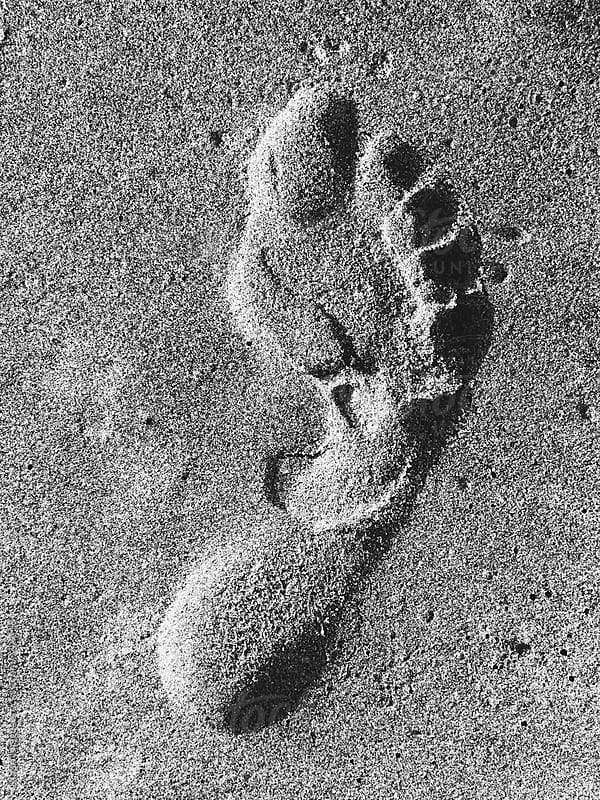 Foot print on beach, close up by Paul Edmondson for Stocksy United