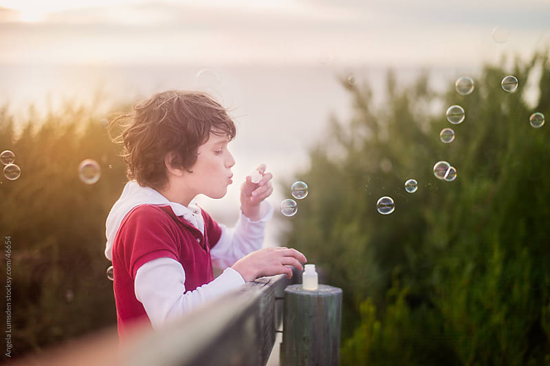 Boy blowing bubbles at sunset by Angela Lumsden for Stocksy United