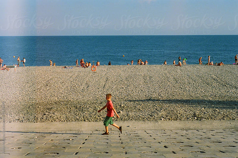A young boy walking on a seashore by Anna Malgina for Stocksy United