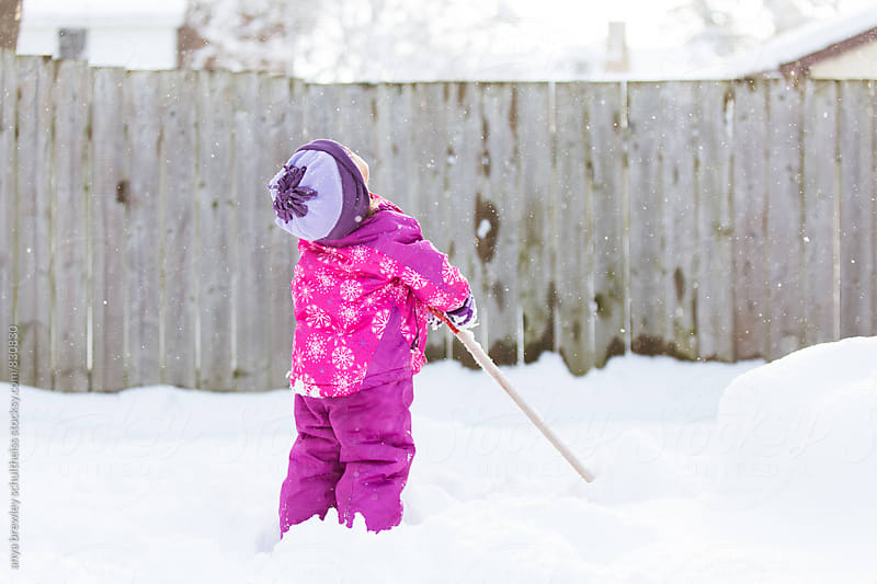 Young girl looking upwards curiously at the snow by anya brewley schultheiss for Stocksy United