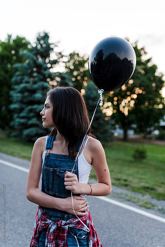 A teenage girl holding a balloon by Chelsea Victoria for Stocksy United