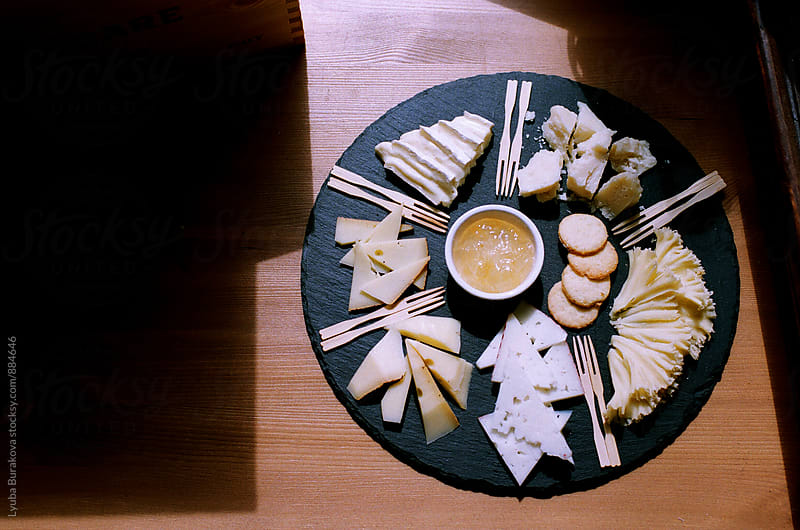 Assorted cheeses on a plate by Lyuba Burakova for Stocksy United