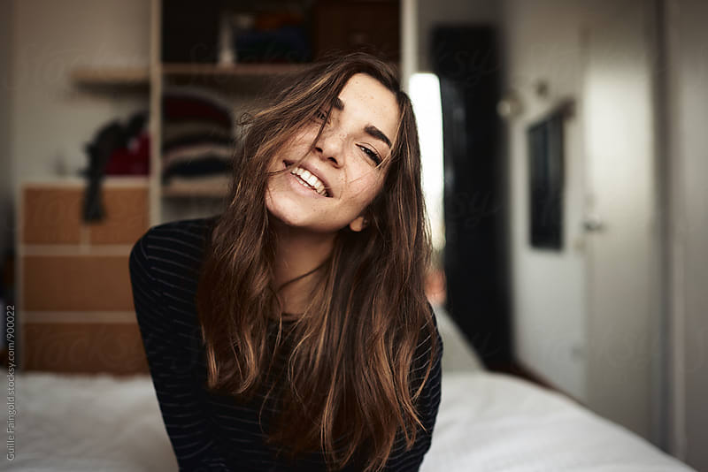 Young woman with long dark hair smiling at camera by Guille Faingold for Stocksy United