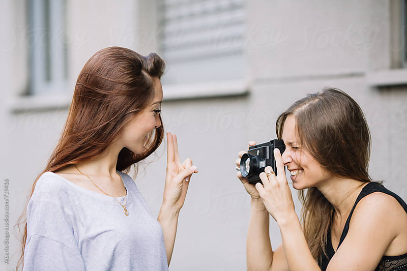 Young women photogrphs her smiling friend with polaroid by Alberto Bogo for Stocksy United