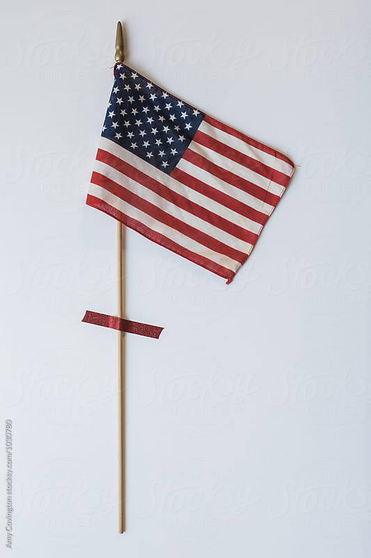 Vintage American Flag taped on a wall by Amy Covington for Stocksy United