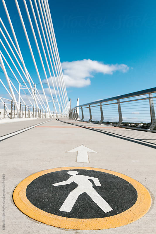 Round bright pedestrian sign and arrow painted on a walking lane of a bridge by Mihael Blikshteyn for Stocksy United