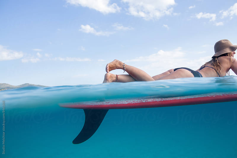 Girl relaxes on her surfboard by Melchior van Nigtevecht for Stocksy United