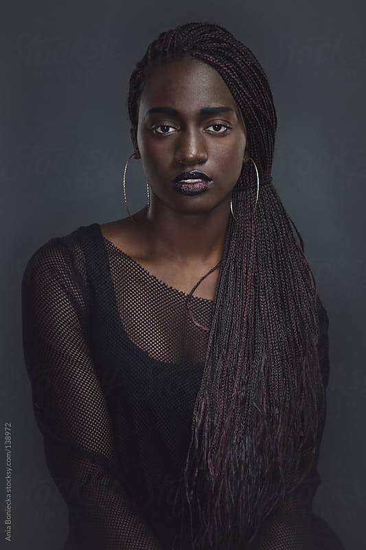 A beautiful black woman with a braided weave by Ania Boniecka for Stocksy United