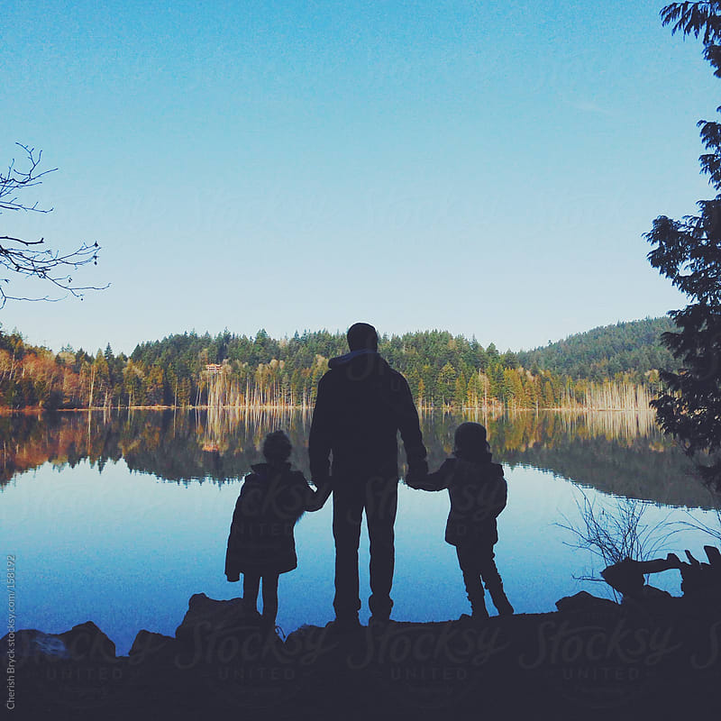 Father and his daughters at the lake by Cherish Bryck for Stocksy United