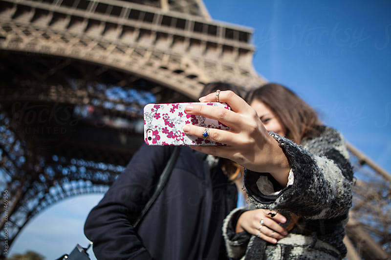 sweet young women taking a selfie under the Eiffel tower, Paris. by kkgas for Stocksy United