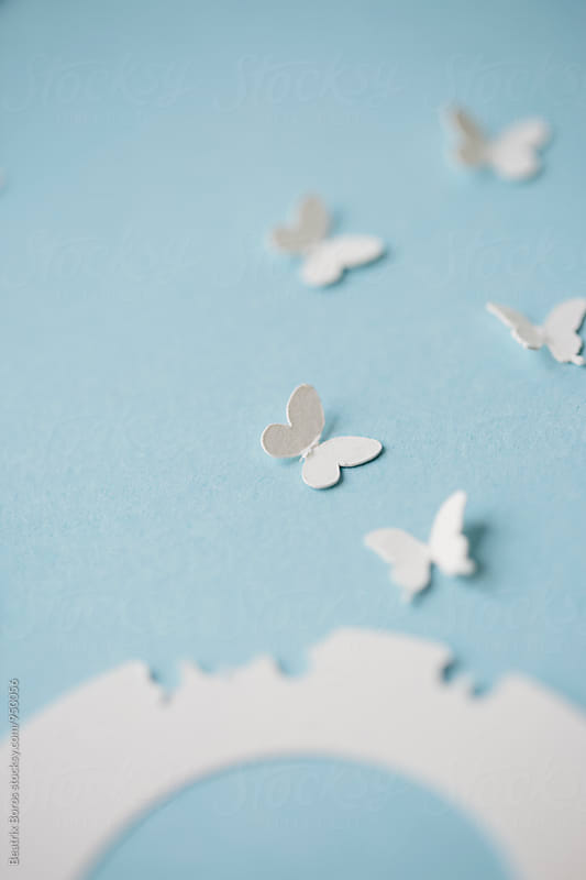 White butterflies flying away from a shape by Beatrix Boros for Stocksy United