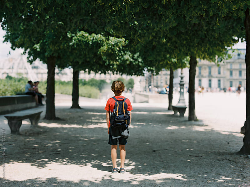 Rear view of boy standing under trees in Paris by Kirstin Mckee for Stocksy United