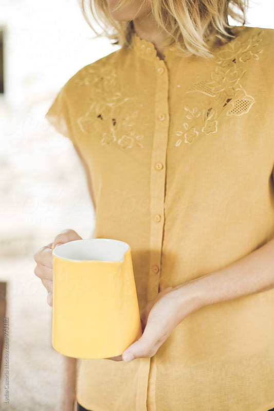 young woman with a vintage shirt  holding a vase of water  by Lydia Cazorla for Stocksy United