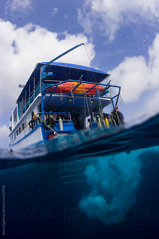 Over/under ocean view of a scuba diving liveaboard boat in Thailand by Soren Egeberg for Stocksy United