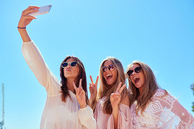 Three girls taking selfie while showing peace signs and smiling by Guille Faingold for Stocksy United