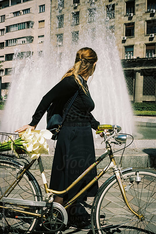 A girl with flowers and a bike by Aleksandra Martinovic for Stocksy United