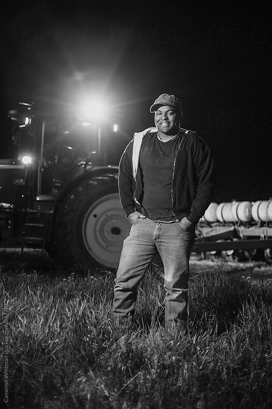 African American Farmer Portrait With His Tractor At Night by Cameron Whitman for Stocksy United